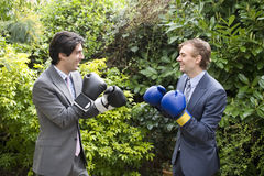 Two young men in suits stage a mock boxing match Stock Images