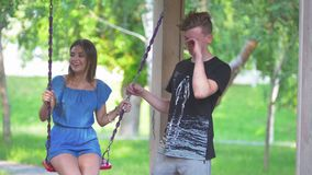 Two young men swings on swing of their beautiful girls in summer park. Slow motion stock video