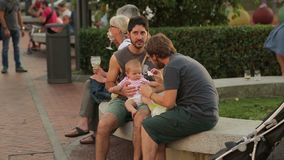 Two young men taking care of child, feeding baby girl in the park, babysitting. Stock footage stock footage