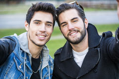 Two young men taking selfie. While outdoors, point of view of the camera itself royalty free stock photos