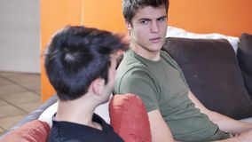 Two young men talking and chatting. Two young male friends talking and chatting while sitting on sofa at home, relaxing and having fun together stock footage
