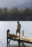 Two young men talking on lake jetty, man leaning against wooden post, using laptop, profile Stock Image