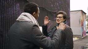 Two young men talking in the street and giving a high five. Two young people in coats talking in an autumn street and giving a high five. The concept of stock video footage