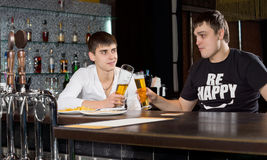 Two young men toasting each other over a beer. Clinking their glasses as they celebrate a special event while sitting at the bar counter Stock Image