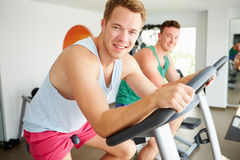 Two Young Men Training In Gym On Cycling Machines Together. Looking At Camera Smiling Stock Photos