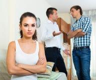 Two young men and unhappy girl Stock Photos