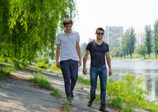Two young men walking along a riverbank. Two young men enjoy the warm sunshine and beautiful scenery while walking along a riverbank Royalty Free Stock Images