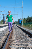 Two young men walking on the rail track Stock Photos