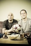 Two young men watching a football match on tv. Sport fans Royalty Free Stock Image