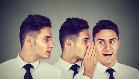 Two young men whispering each other and to astonished guy in the ear. stock photos
