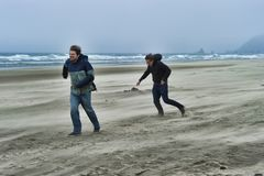 Two young men on a windy beach. Brothers brave the windy cold wet weather at Cannon Beach on the Oregon Coast stock photos