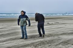 Two young men on a windy beach. Two brothers brave the windy cold wet weather at Cannon Beach on the Oregon Coast stock photo
