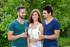 Two young men and a woman, at a garden party. Royalty Free Stock Image