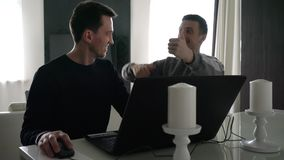Two young men work with a laptop. And enjoy success stock video footage