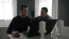 Two young men work with a laptop. And enjoy success stock footage