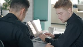 Two young men working on project together in modern office, looking to laptop. Concept of: business people, office interior, laptop on desk, project management stock footage