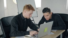Two young men working using laptop in workplace in modern office. Two young men working using laptop in workplace in modern office, male colleagues talking stock video footage