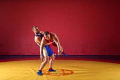 Two young men wrestlers. Two strong wrestlers in blue and red wrestling tights are wrestlng and making a making a hip throw on a yellow wrestling carpet in the royalty free stock photos