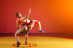 Two young men wrestlers. Two strong wrestlers in blue and red wrestling tights are wrestlng and making a making a hip throw on a yellow wrestling carpet in the royalty free stock images