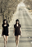 Two young models. Two couple of young models parading in the middle of the road stock images