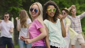 Two young models dancing with friends at music festival, happiness and joy