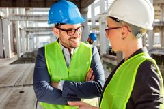 Free Two Young Modern Architects Or Civil Engineers Talking About Future Project Development On A Construction Site Stock Photos - 145102993