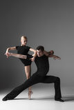 Two young modern ballet dancers on gray studio. The two young modern ballet dancers in black suits posing over gray studio background Stock Image