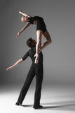 Two young modern ballet dancers on gray studio. The two young modern ballet dancers in black suits posing over gray studio background Royalty Free Stock Image