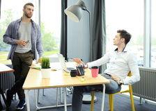 Two young modern men discussing work in the office studio. Stock Image