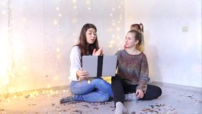 Two young mothers sit on floor in living room and choose new dresses for holidays in online store. Two young women sit on floor in living room and choose new stock footage