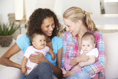 Two Young Mothers On Sofa At Home Stock Photo