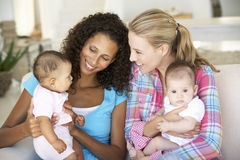 Two Young Mothers On Sofa At Home Stock Images