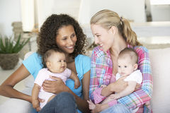 Two Young Mothers On Sofa At Home Royalty Free Stock Photo