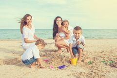 Two young mothers and their children having fun on the beach Royalty Free Stock Images