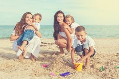 Two young mothers and their children having fun on the beach Stock Photo