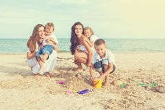 Two young mothers and their children having fun on the beach Stock Photos