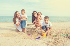 Two young mothers and their children having fun on the beach Royalty Free Stock Photography