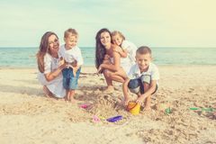 Two young mothers and their children having fun on the beach Royalty Free Stock Photo