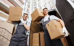Two young movers are at their work near their car in a courtyard royalty free stock image