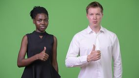 Two young multi-ethnic business couple giving thumbs up together. Studio shot of young beautiful African businesswoman and young handsome Scandinavian stock footage