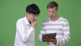 Two young multi-ethnic businessmen having meeting with digital tablet together. Studio shot of young Asian businessman and young Scandinavian businessman stock footage