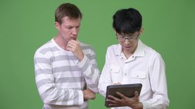 Two young multi-ethnic businessmen having meeting with digital tablet together. Studio shot of young Asian businessman and young Scandinavian businessman stock video