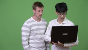 Two young multi-ethnic businessmen having meeting with laptop together. Studio shot of young Asian businessman and young Scandinavian businessman together stock footage