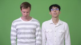 Two young multi-ethnic businessmen looking in opposite directions. Studio shot of young Asian businessman and young Scandinavian businessman together against stock footage