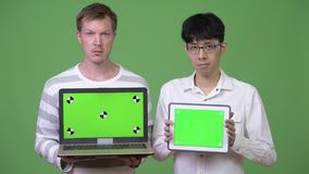 Two young multi-ethnic businessmen showing laptop and digital tablet to the camera. Studio shot of young Asian businessman and young Scandinavian businessman stock video