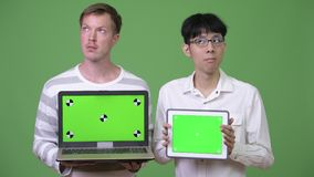 Two young multi-ethnic businessmen showing laptop and digital tablet to the camera. Studio shot of young Asian businessman and young Scandinavian businessman stock video footage