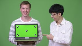 Two young multi-ethnic businessmen showing laptop to the camera while pointing finger. Studio shot of young Asian businessman and young Scandinavian businessman stock video footage