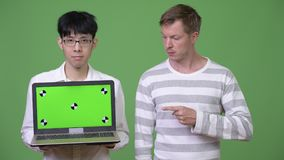 Two young multi-ethnic businessmen showing laptop to the camera while pointing finger. Studio shot of young Asian businessman and young Scandinavian businessman stock video