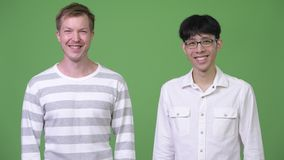 Two young multi-ethnic businessmen smiling together against green background. Studio shot of young Asian businessman and young Scandinavian businessman together stock footage