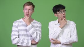 Two young multi-ethnic businessmen thinking together. Studio shot of young Asian businessman and young Scandinavian businessman together against chroma key with stock footage